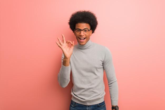 Junger schwarzer mann über einer rosa wand nett und überzeugt, okaygeste tuend