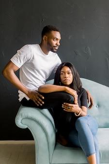 Junger schwarzer mann und afroamerikanisches mädchen auf dunklem hintergrund, der auf einem blauen sofa sitzt. modeporträt des jungen mannes und der jungen frau im studio