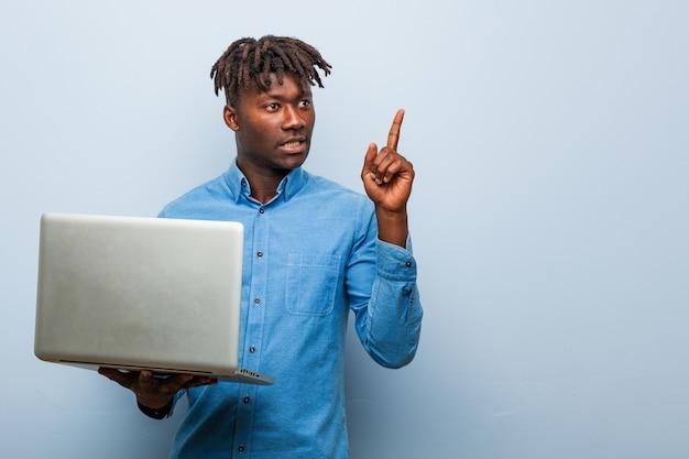 Junger schwarzer rasta mann, der einen laptop hält, der fröhlich mit zeigefinger weg zeigt.