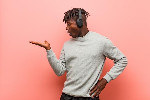 Junger schwarzer rasta-mann, der musik mit kopfhörern hört, beeindruckt, leerzeichen auf handfläche haltend.
