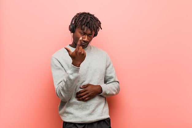 Junger schwarzer rasta-mann, der musik mit kopfhörern hört, die mit dem finger auf sie zeigen, als ob die einladung näher kommt.