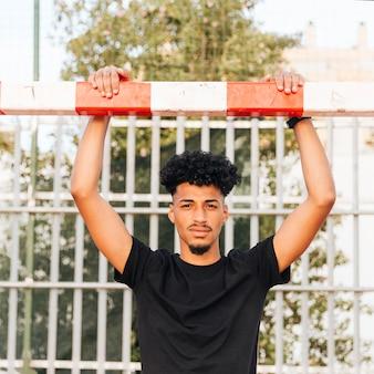 Junger schwarzer sportler, der an fußballziel am stadion hält