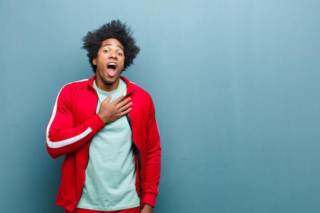 Junger schwarzer sportler, der sich schockiert, erstaunt und überrascht fühlt, mit der hand auf der brust und offenem mund und sagt, wer, ich? gegen grunge wand