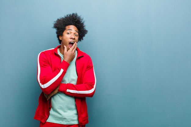 Junger schwarzer sportler mit offenem mund vor schock und unglauben, die hand auf wange und arm gekreuzt