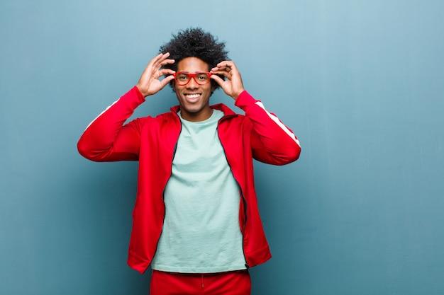 Junger schwarzer sportmann, der entsetzt, überrascht und überrascht sich fühlt und gläser mit erstauntem, ungläubigem blick gegen schmutzwand hält