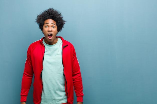 Junger schwarzer sportmann, der entsetzt, verärgert, gestört oder enttäuscht, mit offenem mund und wütend gegen schmutzwand schaut