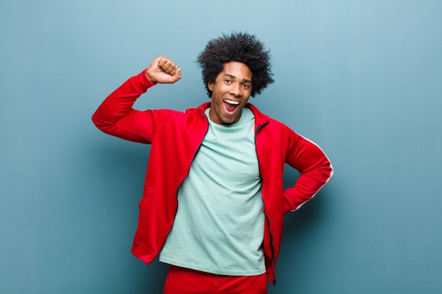Junger schwarzer sportmann, der ernst, stark und rebellisch sich fühlt, faust oben anhebt, für revolution gegen schmutz protestiert oder kämpft