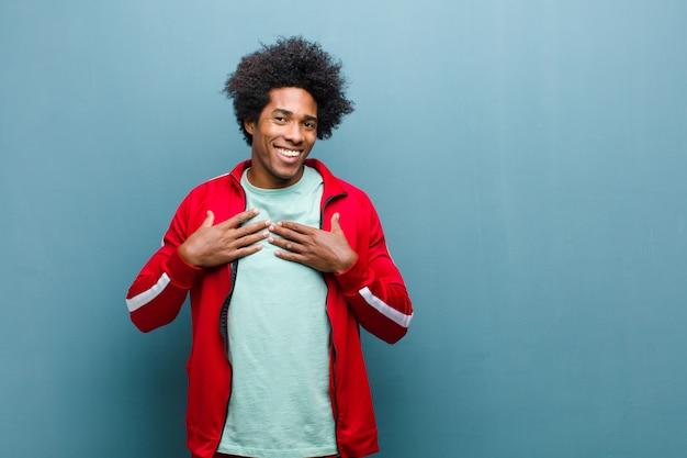 Junger schwarzer sportmann, der glücklich, überrascht, stolz und aufgeregt schaut und auf selbst gegen schmutzwand zeigt