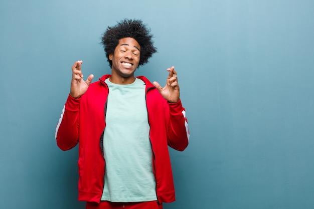 Junger schwarzer sportmann, der nervös und hoffnungsvoll sich fühlt, finger kreuzt, für gutes glück gegen schmutzwand betet und hofft