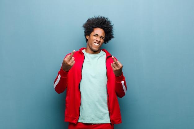 Junger schwarzer sportmann, der provokativ, aggressiv und obszön sich fühlt und den mittelfinger, mit einer rebellischen haltung gegen schmutzwand leicht schlägt