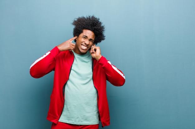Junger schwarzer sportmann, der verärgert, betont und gestört schaut und beide ohren zu ohrenbetäubenden geräuschen, ton oder lauter musik gegen schmutzwand bedeckt