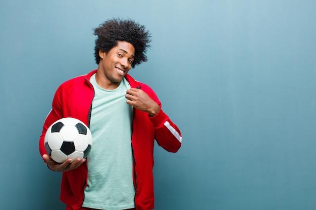 Junger schwarzer sportmann mit einem blauen schmutz wa der fußballkugel