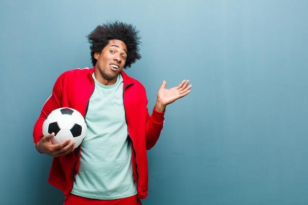 Junger schwarzer sportmann mit einem fußball