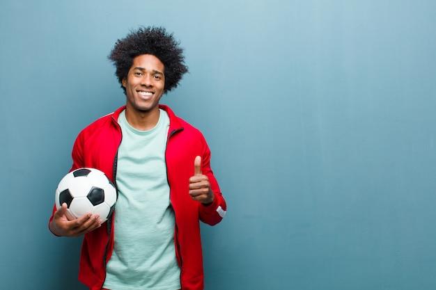 Junger schwarzer sportmann mit einer fußballkugel gegen blaues grunge wa