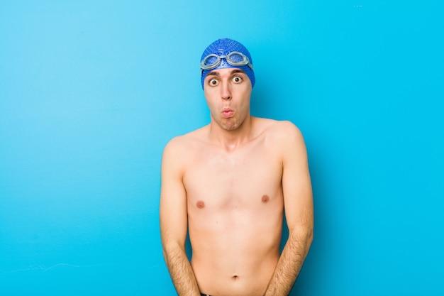 Junger schwimmer zuckt verwirrt mit den schultern und den offenen augen.