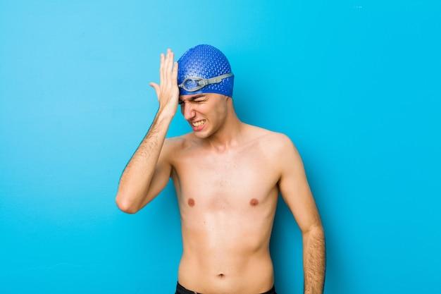 Junger schwimmermann, der etwas vergisst, stirn mit palme schlägt und augen schließt.