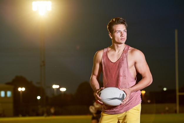 Junger schwitzender amerikanischer fußballspieler, der mit einem ball auf dem stadion aufwirft