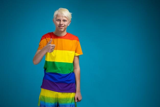 Junger schwuler blonder kerl mit blauen augen in der lgbt-gemeinschaftskleidung regenbogen auf blauem hintergrund