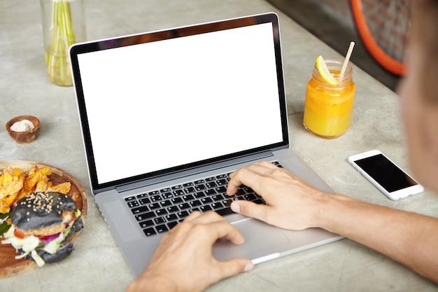 Junger selbständiger mann, der an seinem projekt auf allgemeinem laptop arbeitet, während er im café sitzt und freies wi-fi benutzt. männlicher student, der internet durchsucht oder e-mail auf elektronischem gerät während des mittagessens überprüft