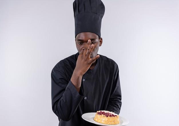 Junger selbstbewusster afroamerikanischer koch in der kochuniform hält kuchen auf teller und gestikuliert köstliches zeichen auf weiß mit kopienraum