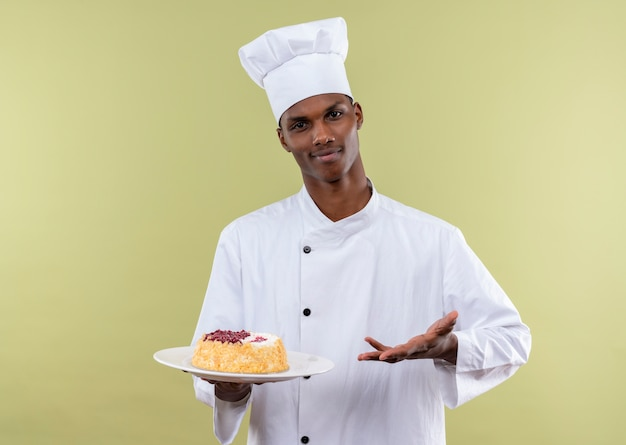 Junger selbstbewusster afroamerikanischer koch in der kochuniform hält kuchen auf teller und zeigt mit hand lokalisiert auf grünem hintergrund mit kopienraum