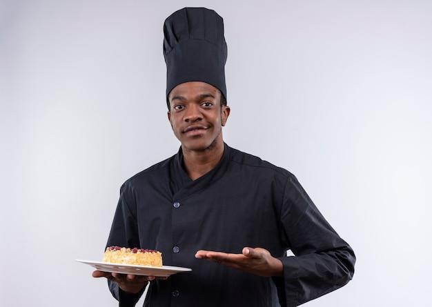 Junger selbstbewusster afroamerikanischer koch in der kochuniform hält kuchen auf teller und zeigt mit hand lokalisiert auf weißem hintergrund mit kopienraum
