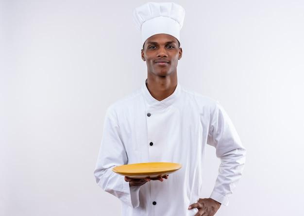 Junger selbstbewusster afroamerikanischer koch in der kochuniform hält leeren teller und legt hand auf taille auf lokalisiertem weißem hintergrund mit kopienraum