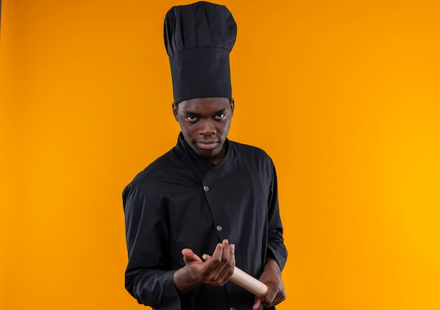 Junger selbstbewusster afroamerikanischer koch in der kochuniform hält nudelholz auf orange mit kopienraum