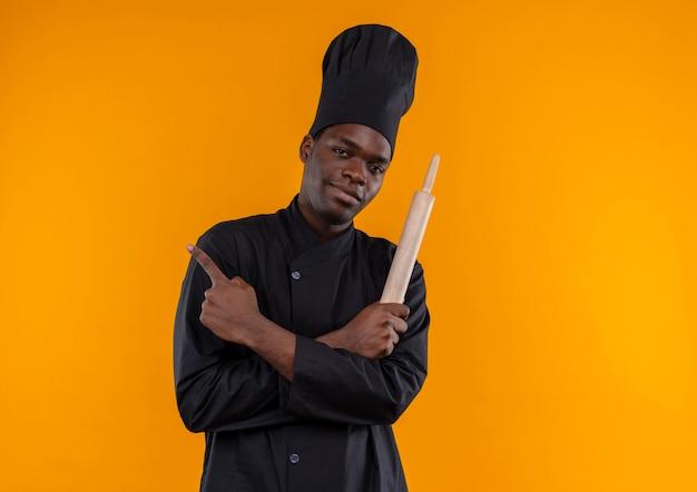 Junger selbstbewusster afroamerikanischer koch in der kochuniform hält nudelholz mit verschränkten armen auf orange mit kopienraum