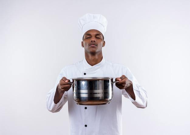 Junger selbstbewusster afroamerikanischer koch in der kochuniform hält topf mit geschlossenen augen auf lokalisiertem weißem hintergrund mit kopienraum