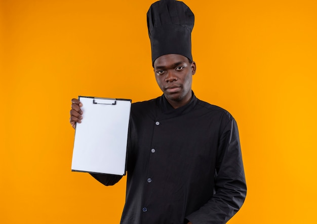 Junger selbstbewusster afroamerikanischer koch in der kochuniform hält zwischenablage auf orange mit kopienraum