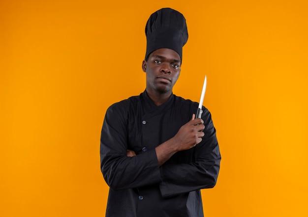 Junger selbstbewusster afroamerikanischer koch in der kochuniform verschränkt die arme und hält messer, das kamera auf orange mit kopienraum betrachtet