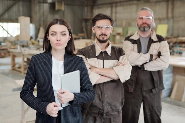 Junger selbstbewusster arbeiter in uniform und schutzbrille, der auf die skizze eines neuen möbelstücks zeigt und es dem kollegen erklärt