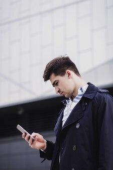 Junger selbstbewusster attraktiver geschäftsmann, der smartphone verwendet