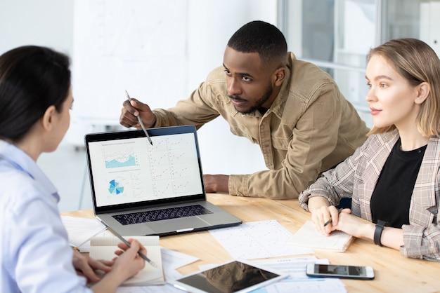 Junger selbstbewusster bankier oder makler, der sich über schreibtisch bückt, während finanzdaten auf laptop-anzeige analysiert werden und kollegen zuhören
