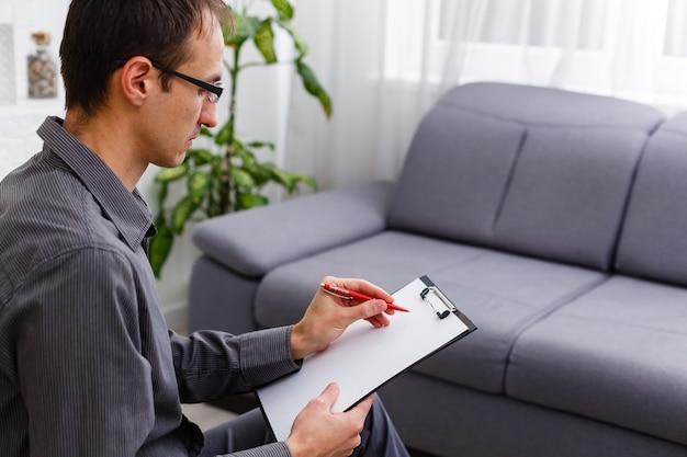 Junger selbstbewusster berater mit stift und dokument, der seinem patienten etwas erklärt