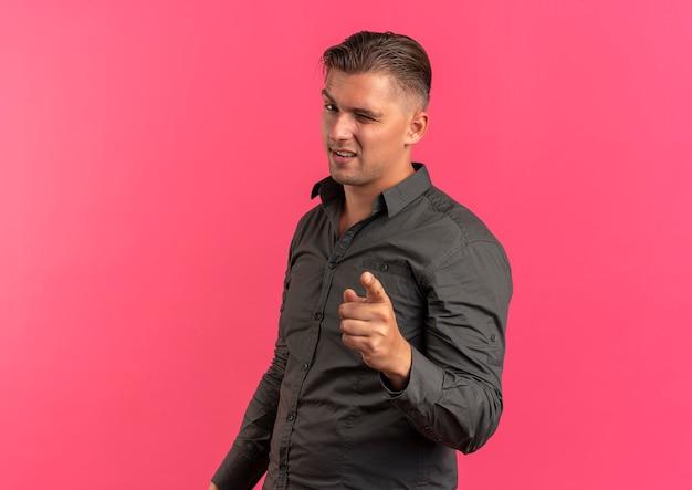 Junger selbstbewusster blonder gutaussehender mann blinzelt auge und zeigt auf kamera