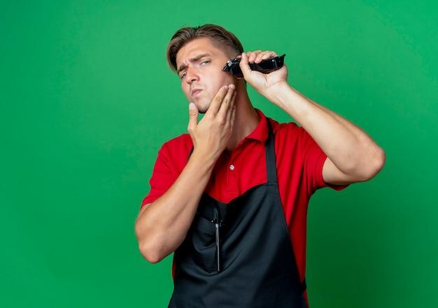 Junger selbstbewusster blonder männlicher friseur in uniform hält bart mit haarschneidemaschine, der auf grünfläche mit kopienraum isoliert wird
