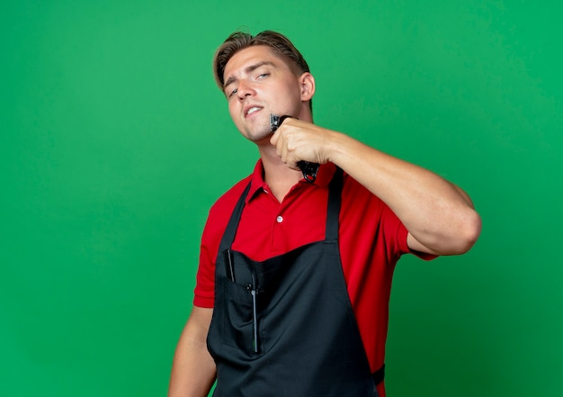 Junger selbstbewusster blonder männlicher friseur in uniform hält haarschneider nahe gesicht lokalisiert auf grünfläche mit kopienraum