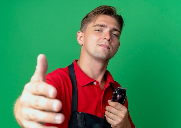 Junger selbstbewusster blonder männlicher friseur in uniform hält hand heraushalten haarschneidemaschine isoliert auf grünfläche mit kopienraum
