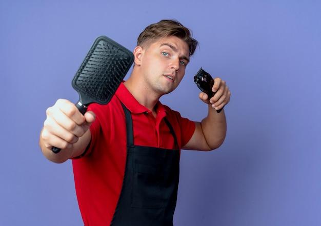 Junger selbstbewusster blonder männlicher friseur in uniform hält kamm und haarschneider lokalisiert auf violettem raum mit kopienraum