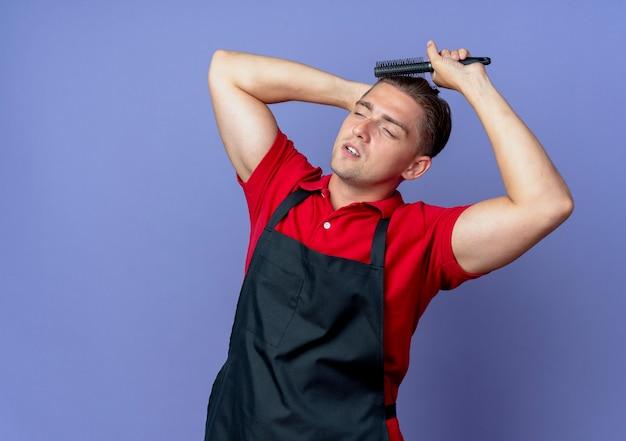 Junger selbstbewusster blonder männlicher friseur in uniform hält kopf hinter kämmendem haar, das seite betrachtet, die auf violettem raum mit kopienraum isoliert ist