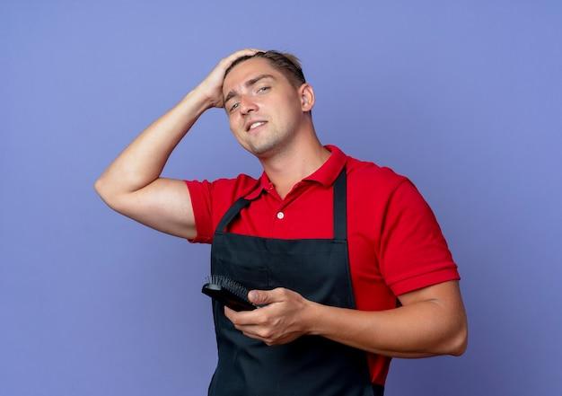 Junger selbstbewusster blonder männlicher friseur in uniform setzt hand auf kopf, der kamm lokalisiert auf violettem raum mit kopienraum isoliert
