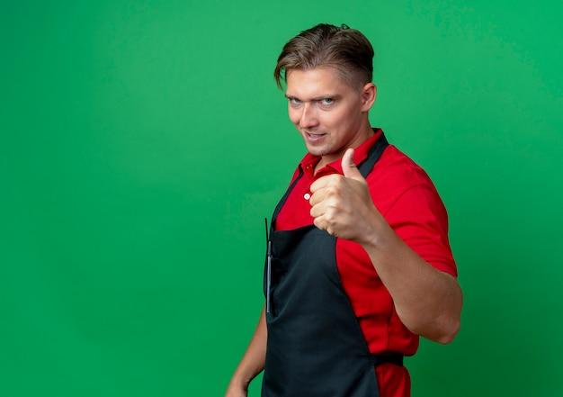 Junger selbstbewusster blonder männlicher friseur in uniform steht seitlich daumen hoch isoliert auf grünfläche mit kopierraum