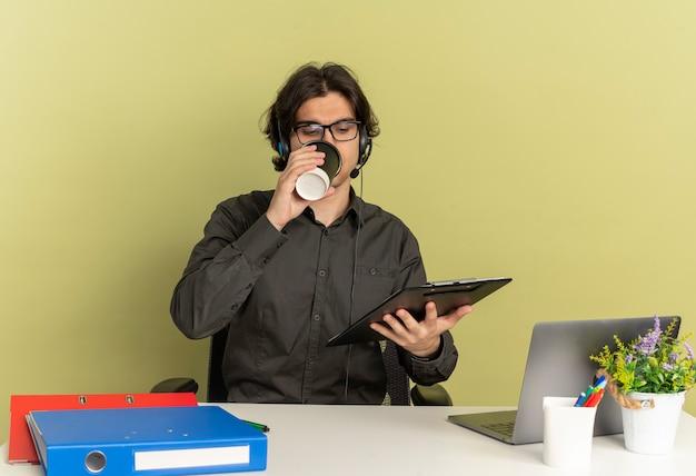 Junger selbstbewusster büroangestellter mann auf kopfhörern in optischen gläsern sitzt am schreibtisch mit bürowerkzeugen unter verwendung des laptops schaut auf zwischenablage, die kaffee von tasse lokalisiert auf grünem hintergrund mit kopienraum trinkt