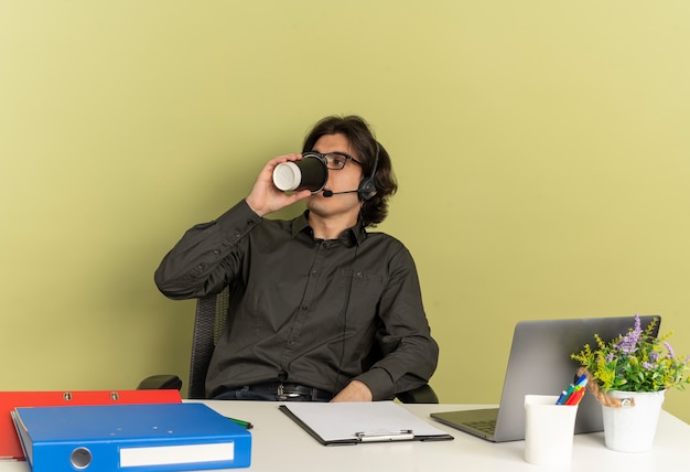 Junger selbstbewusster büroangestellter mann auf kopfhörern in optischen gläsern sitzt am schreibtisch mit bürowerkzeugen unter verwendung von laptop trinkt kaffee aus tasse