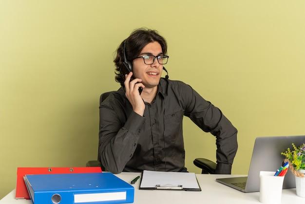 Junger selbstbewusster büroangestellter mann auf kopfhörern in optischen gläsern sitzt am schreibtisch mit bürowerkzeugen unter verwendung von laptopgesprächen am telefon