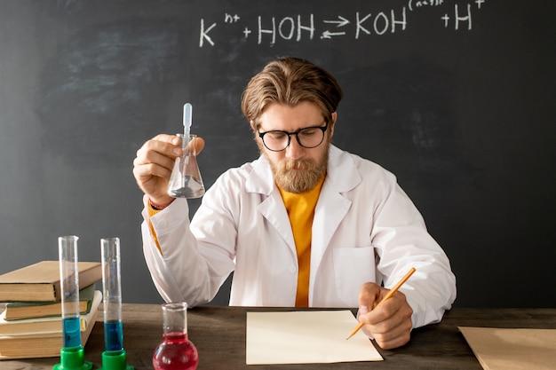 Junger selbstbewusster chemielehrer im weißmantel, der sein online-publikum beim sitzen betrachtet