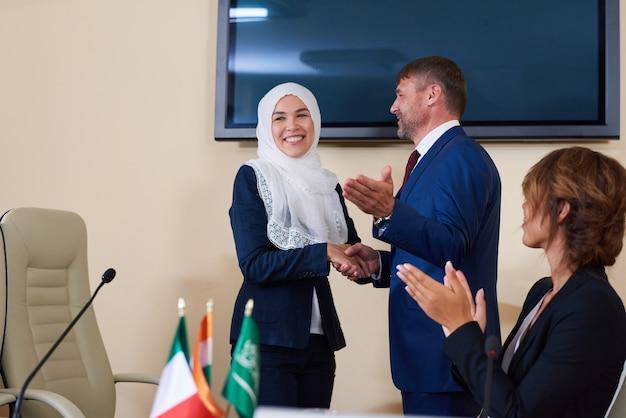 Junger selbstbewusster geschäftsmann, der nach ihrem bericht im forum die hand der erfolgreichen sprecherin im hijab schüttelt