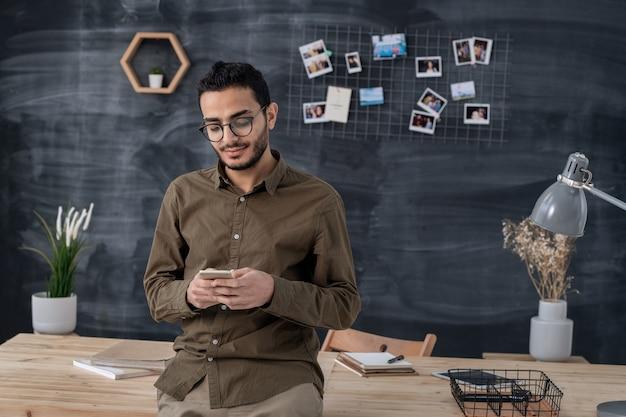Junger selbstbewusster geschäftsmann in der freizeitkleidung, die im smartphone während des stehens durch tisch auf raum der tafel rollt